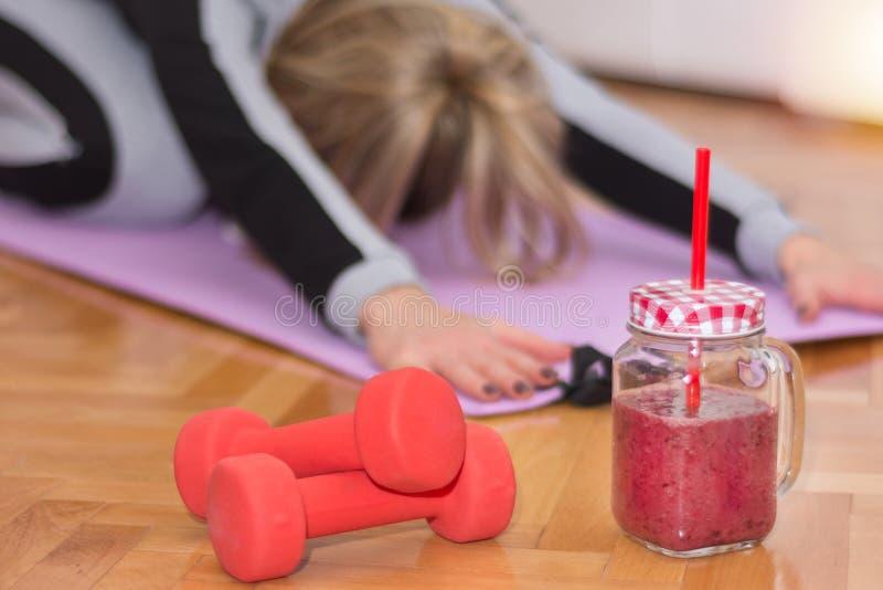 Två röd hantel och smoothie i retro krus på golv och kvinnan som arbetar sträcka övningar royaltyfri foto