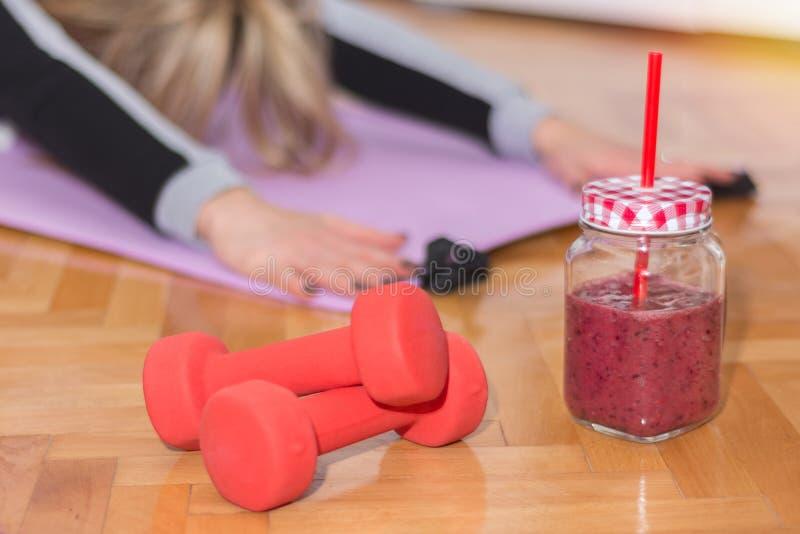 Två röd hantel och smoothie i retro krus på golv och kvinnan som arbetar sträcka övningar royaltyfri bild