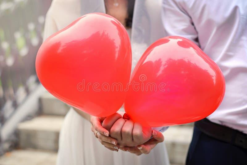 Två röda ballonger i form av hjärtor i händerna av nygifta personerna royaltyfria bilder
