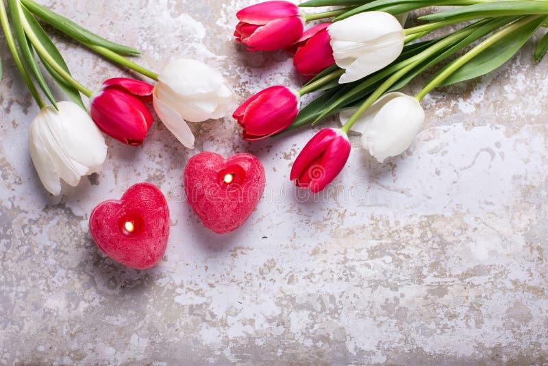 Två röda bränningstearinljus i form av hjärta och den röda och vita tulien arkivbild