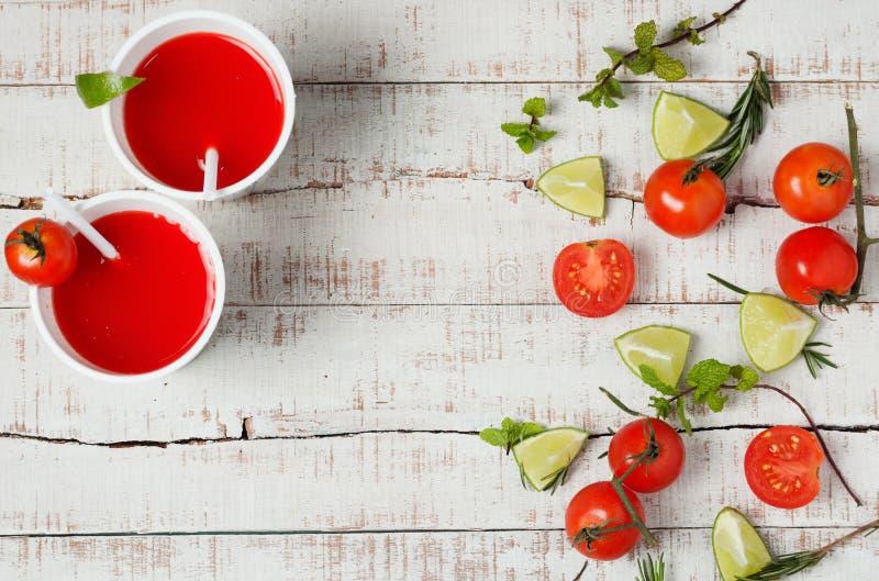 Två röda drinkar med den ny tomaten och limefrukt arkivfoton