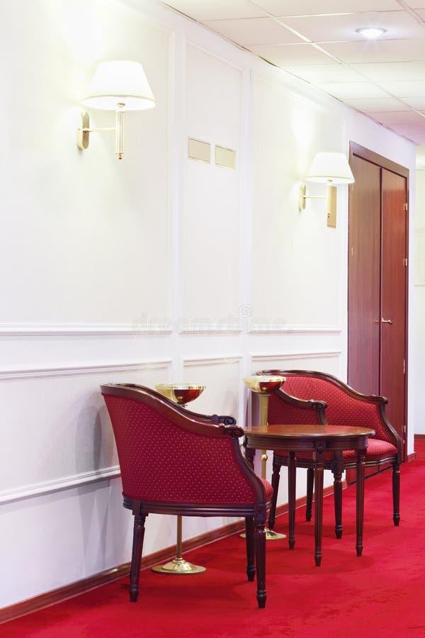 Två röda fåtöljer med den runda trätabellen på röd matta royaltyfri foto