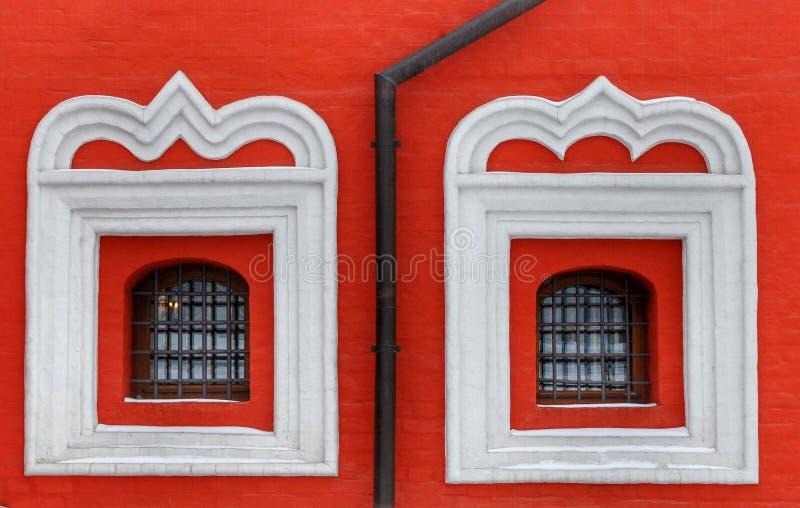 Två röda gallerförsedda kyrkliga fönster arkivfoton