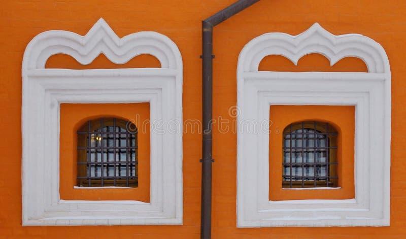 Två röda gallerförsedda kyrkliga fönster royaltyfri foto