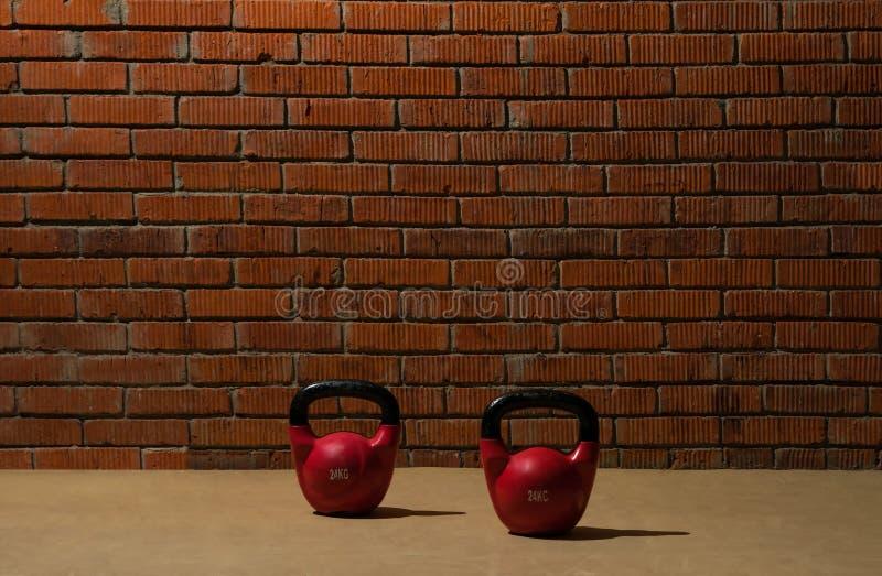 Två röda hantlar för sportar står på golvet nära tegelstenväggen arkivfoton