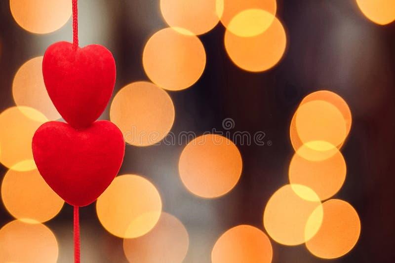 Två röda hjärtor, bakgrund för anbud för stillhet för närbildbokehafton fotografering för bildbyråer