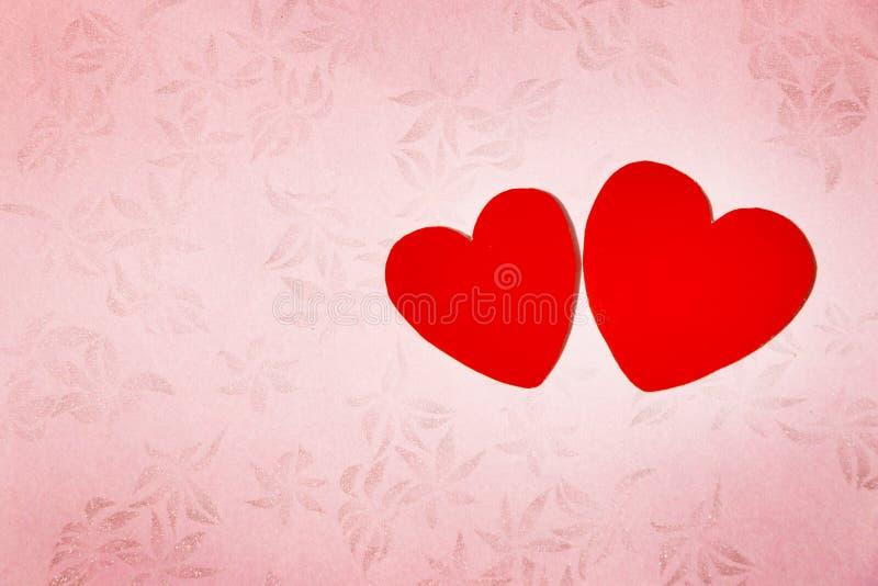 Två röda hjärtor i rosa blom- modellbakgrund royaltyfria foton