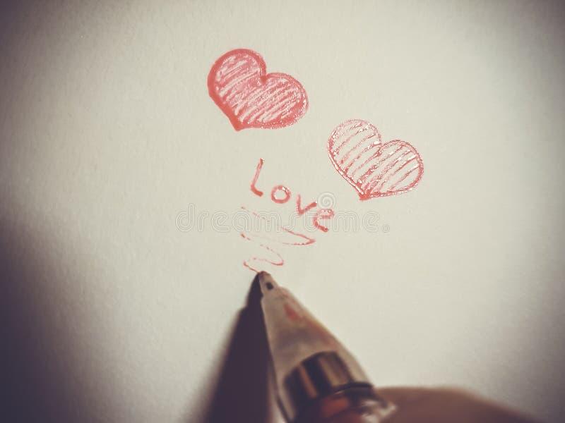 Två röda hjärtor och en penna på en ljus bakgrund arkivfoto