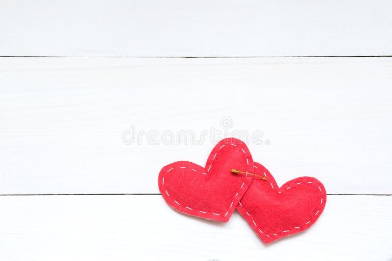 Två röda hjärtor och säkerhetsnål på den vita bakgrunden, valentindagbegrepp arkivbilder
