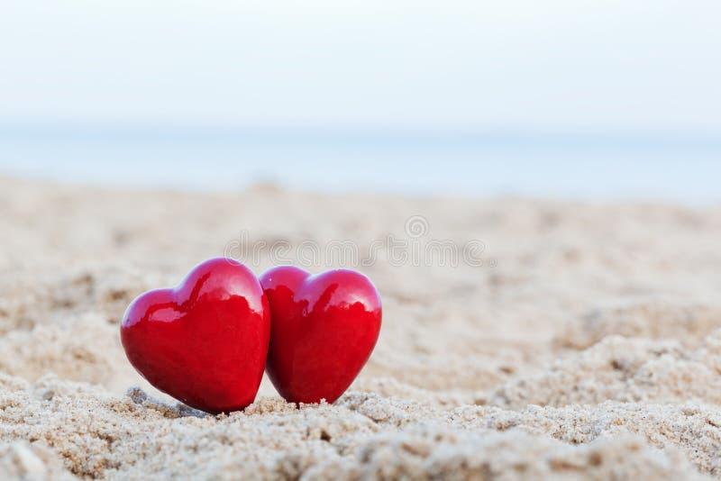 Två röda hjärtor på stranden. Förälskelse arkivbilder