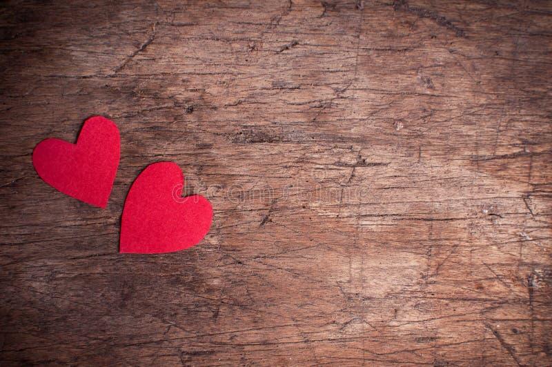 Två röda hjärtor på trätabellen arkivbild