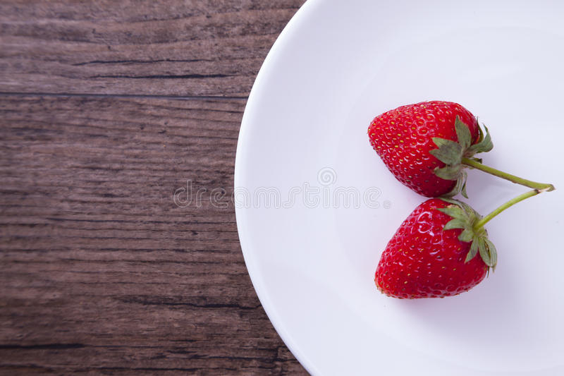Två röda jordgubbar i den vita maträtten royaltyfria bilder