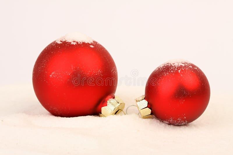 Två röda matt julbollar på snö royaltyfri foto