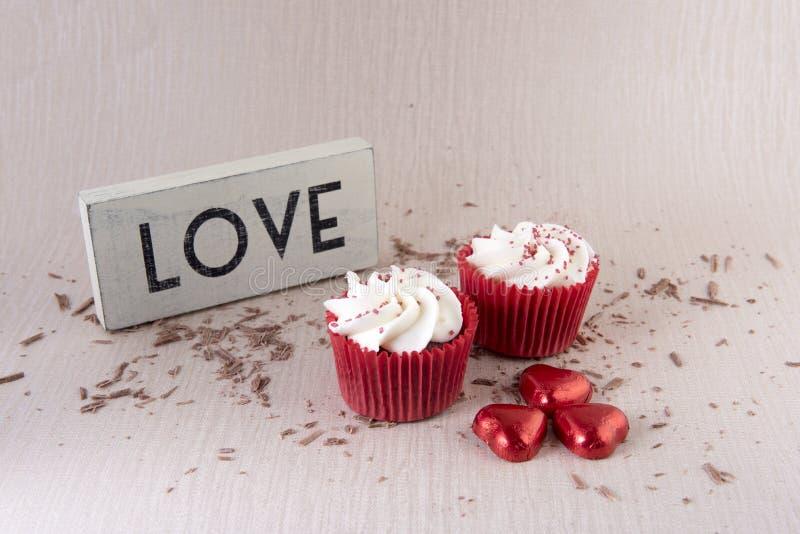 Två röda sammetmuffin med chokladstänk arkivfoto