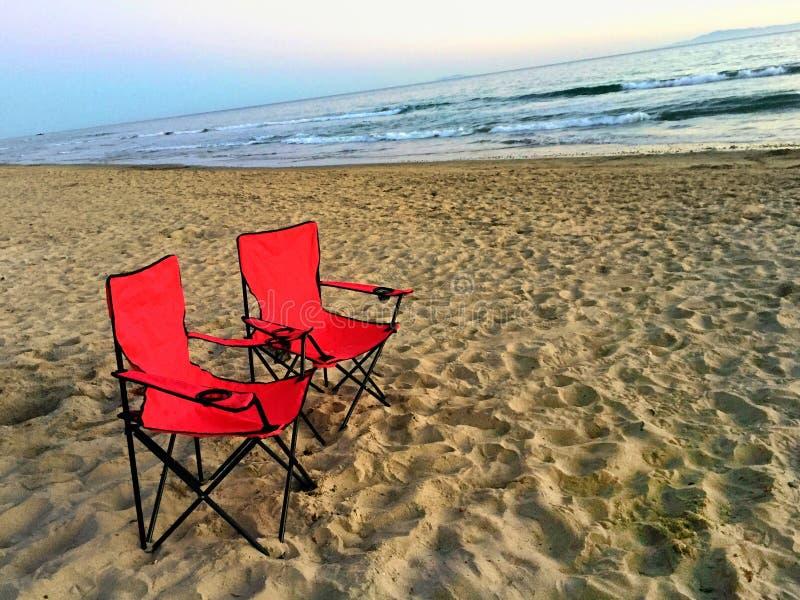 Två röda stolar på stranden som förbiser havet royaltyfri bild