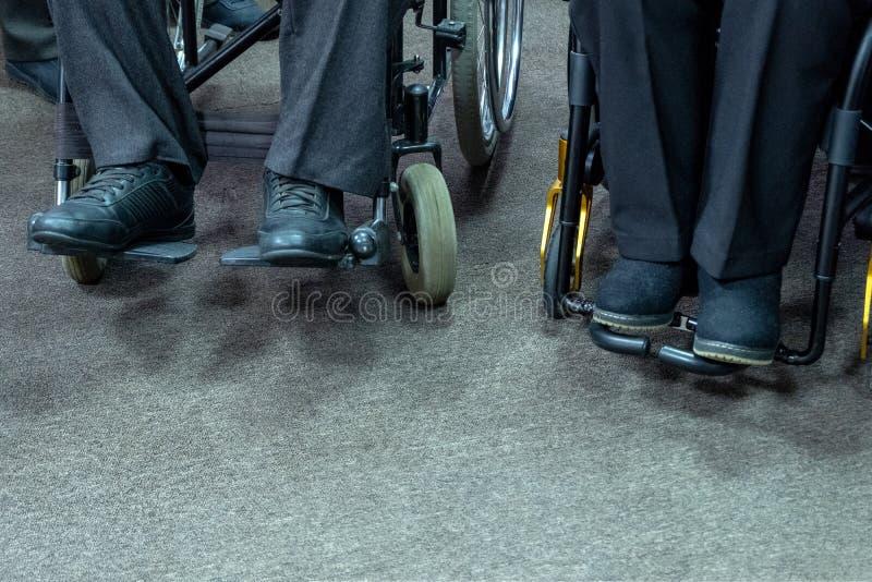 Två rörelsehindrade personer sitter i rullstolar Närbild av ben Copyspace royaltyfri foto
