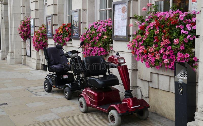 Två rörlighetssparkcyklar utanför en restaurang i London royaltyfria foton