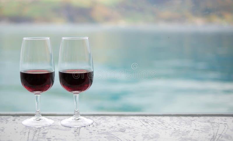 Två rött vinexponeringsglas på stång över suddighet gör grön sjöbakgrund royaltyfri foto