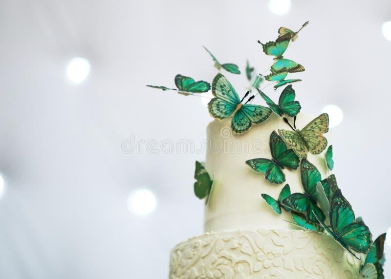 Två-raden bröllopstårtan dekoreras med gröna fjärilar royaltyfri foto