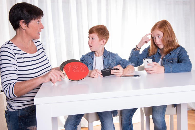 Två redhaired ungar spelar med deras smartphonesmoderwa royaltyfri foto