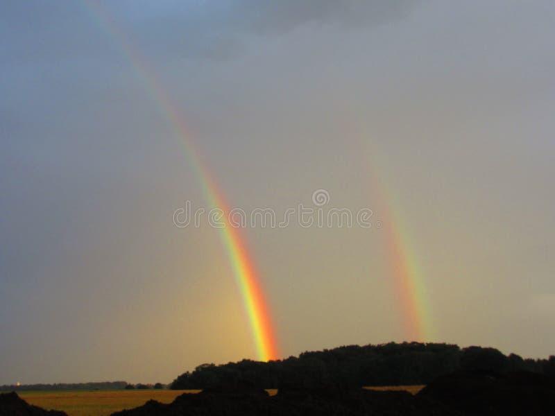 Två regnbågar dubblerar parhimmel arkivfoto