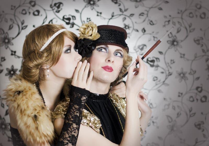 Två retro utformade kvinnor som delar hemligheter royaltyfri bild