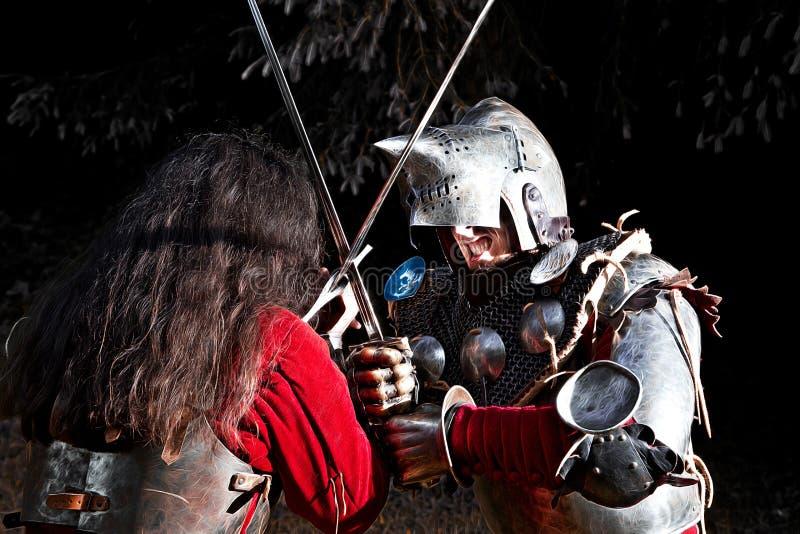 Två riddare som fäktar med svärd i träna på natten royaltyfri bild