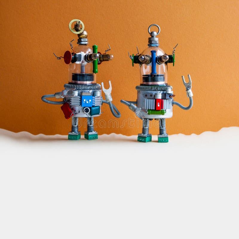 Två robotar för exponeringsglashuvudufo på brun beige bakgrund Den futuristiska robothumanoiden leker med lyftta händer kopiera a royaltyfri foto