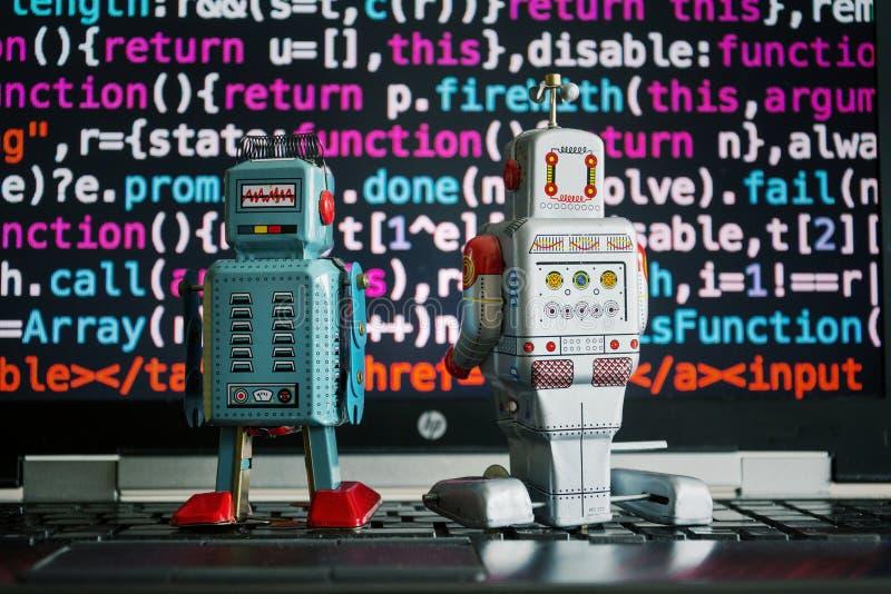 Två robotar som ser bärbar datorskärmen med källkoden, konstgjord intelligens, stora data och lär djupt royaltyfria bilder