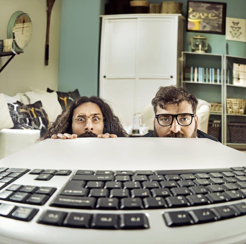 Två roliga datorscientits som stirrar på en keybord arkivbilder
