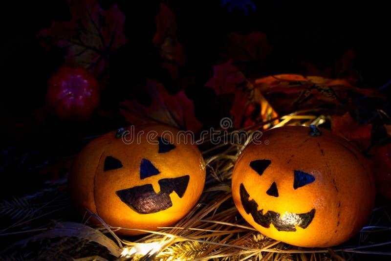 Två roliga eller arga pumpor Jack eller Lantern-huvudet tittar på varandra, ljuset lyser på deras ansikte, på hö royaltyfri bild