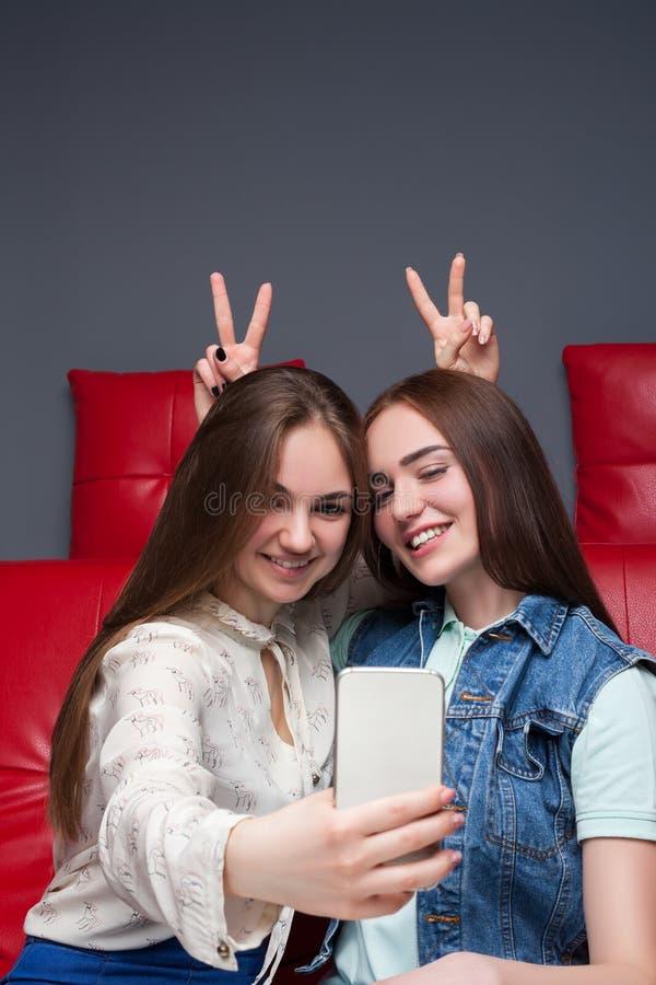 Två roliga flickvänner gör selfie på kamera royaltyfri foto