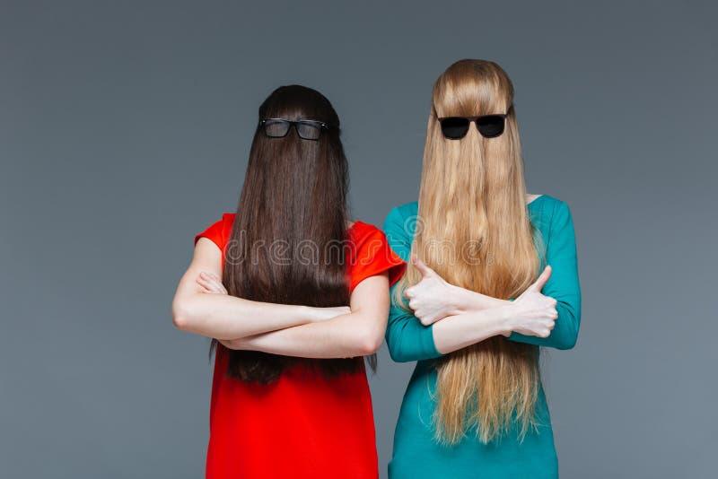Två roliga kvinnor täckt framsida med långt hår royaltyfri bild