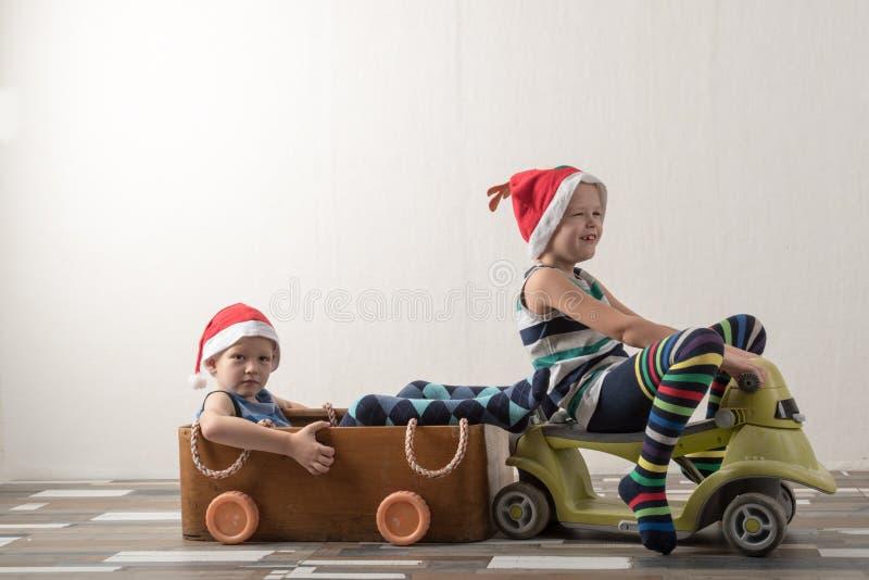 Två roliga pojkar i en Santa Claus hatt spelar med hästar som dras på papp Grabbarna har gyckel hemma Julferieconce arkivbild