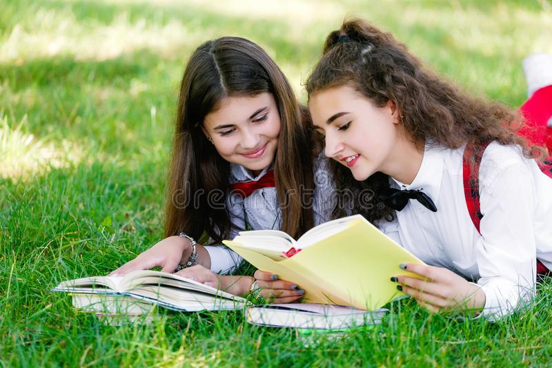 Två roliga skolflickor ligger på gräset och läseböckerna Flickor flickvänner, systrar undervisas kurser i natur arkivfoton