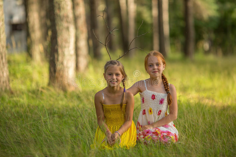 Två roliga små flickor poserar för ett foto i parkera Lyckligt royaltyfria bilder
