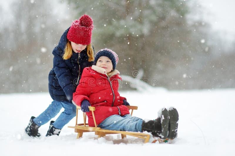 Två roliga små flickor som har gyckel med en släde i härlig vinter, parkerar Gulliga barn som spelar i en snö royaltyfria bilder