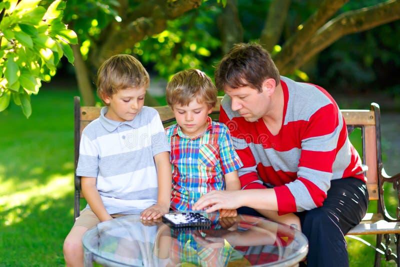 Två roliga stiliga ungepojkar och barnfadern som tillsammans spelar kontrollörer, spelar Söner, syskonbarn och farsautgifter royaltyfri fotografi