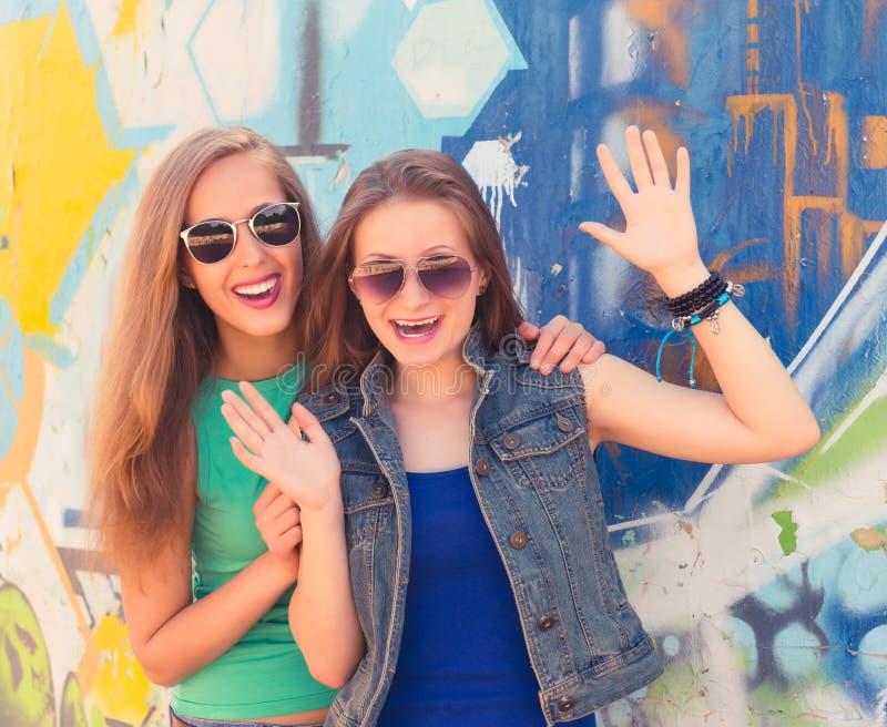 Två roliga tillgivna tonåringvänner som skrattar och har gyckel arkivfoton