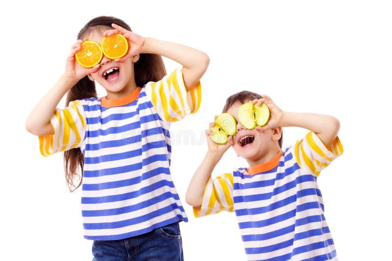Två roliga ungar med frukter synar på fotografering för bildbyråer