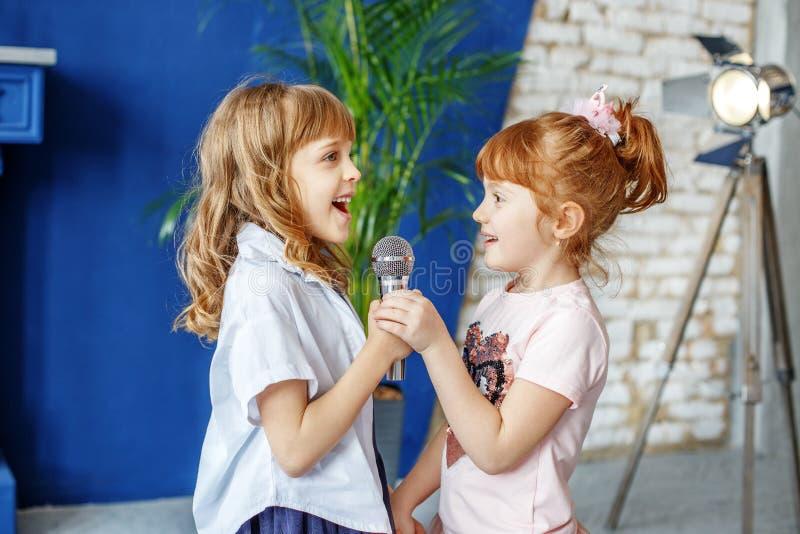 Två roliga ungar sjunger en sång i karaoke Begreppet är barndom, fotografering för bildbyråer