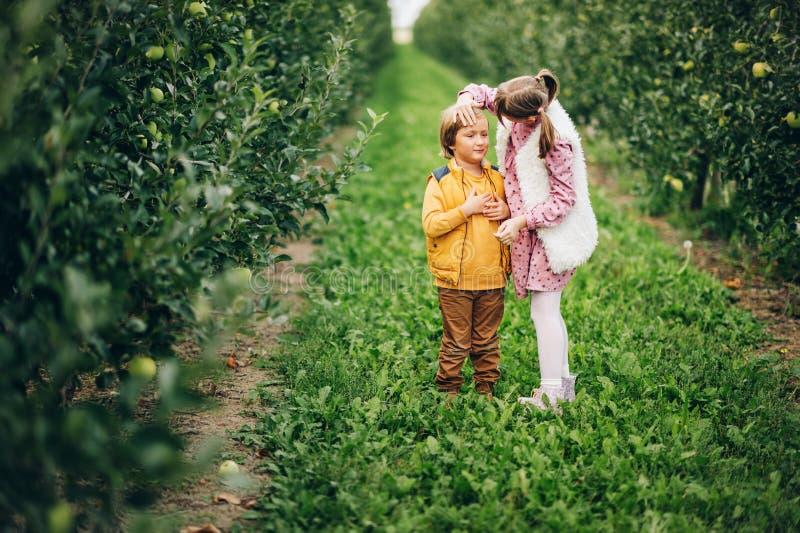 Två roliga ungar som spelar i grön äpplefruktträdgård royaltyfria bilder