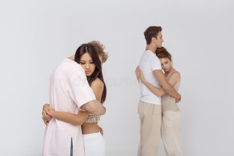 Två romantiska par som är förälskade inomhus mot vit arkivfoton