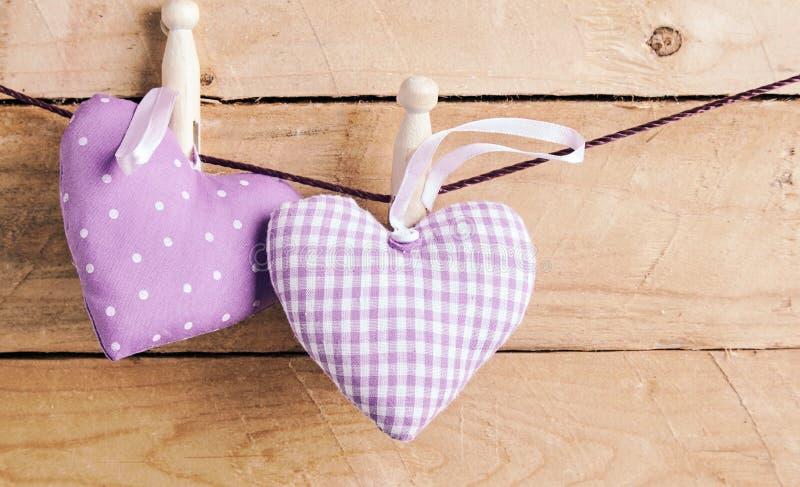 Två romantiska purpurfärgade hjärtor som fixeras på en linje royaltyfri bild