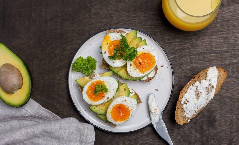Två rostade bröd med avokadot och det kokta ägget på kornbröd på den vita plattan arkivfoto