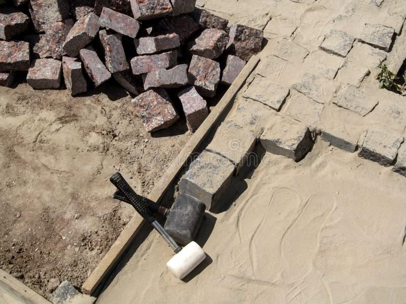 Två rubber klubbor bland en hög av granitstenar för att stenlägga royaltyfria foton