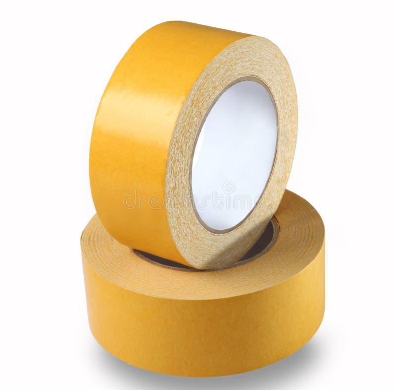 Två rullar av det gula tvåsidiga bandet på en vit bakgrund, iso arkivfoto