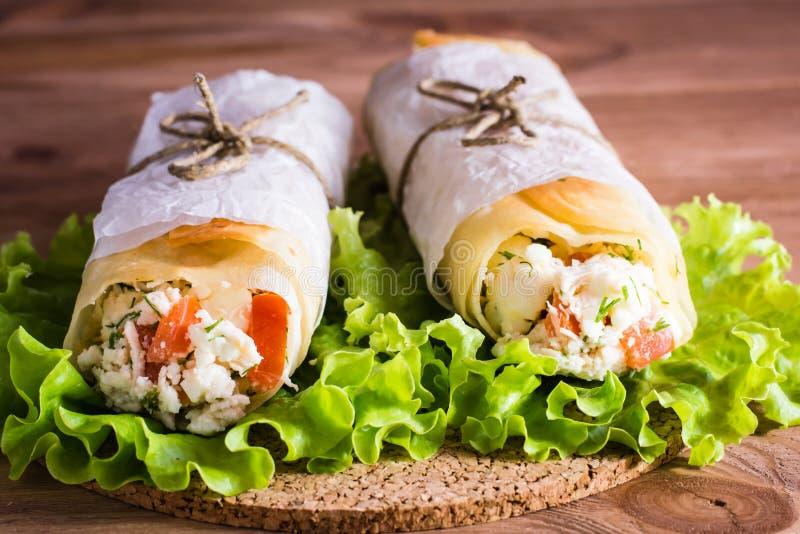 Två rullar av pitabröd som är välfyllda med ost, höna och tomater fotografering för bildbyråer