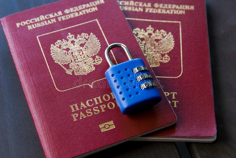 Två ryska pass som låsas till hänglåset Symbol av anti--ryss sanktioner arkivbild