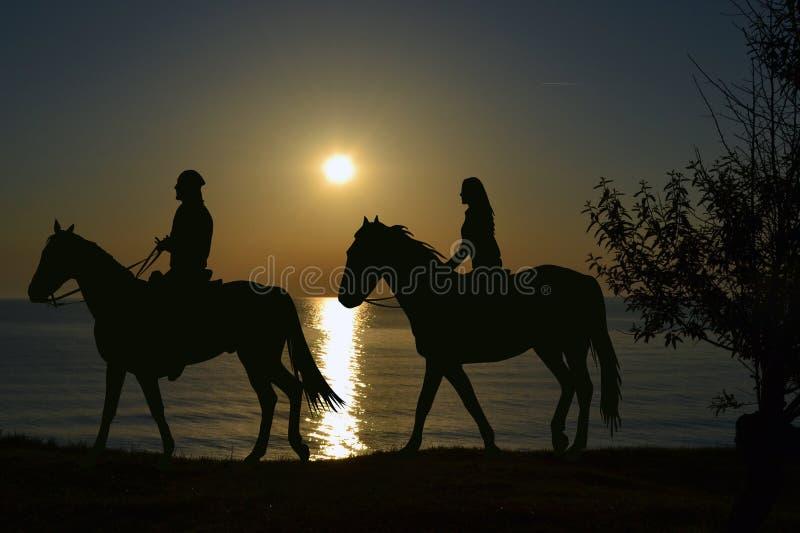 Två ryttare som rider under solnedgång på kusten arkivbild